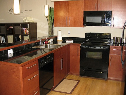 Kitchen with dark colored granite top counters